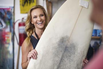 Surfboard shaper workshop, female employee smiling with surfboard
