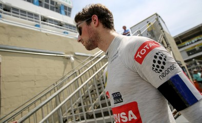 Lotus Formula One driver Romain Grosjean of France wears a French national flag on his left arm after the qualifying session for the Brazilian F1 Grand Prix in Sao Paulo