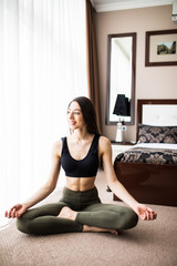 Young attractive smiling woman practicing yoga, sitting in Half Lotus exercise, Ardha Padmasana pose, home interior, cat near