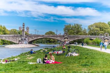 Isar in München nahe der Wittelsbacherbrücke mit Erholungssuchenden am Isarstrand