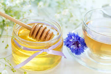 Honey in glass jars and cup of tea