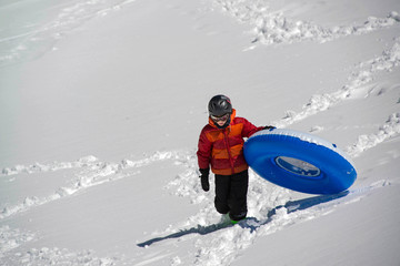 Teenage boy carrying blue blowup inflatable sledding tube up snowy hill