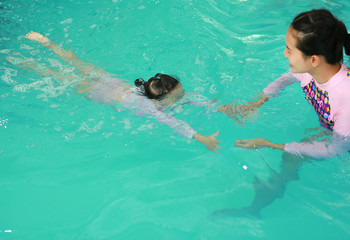 family of mother teaching kid diving in swimming pool.