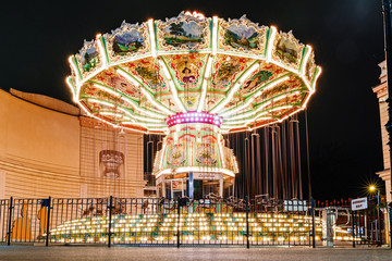 Children's Carousel at an amusement park in the evening with night lights illumination
