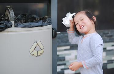 Cute little girl putting waste in the bin outdoor.