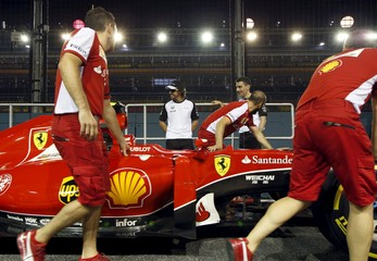 McLaren Honda Formula One driver Fernando Alonso of Spain speaks to his former teammates from Ferrari as they push a car past at the pit ahead of the Singapore F1 Grand Prix night race in Singapore