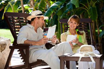 couple souriant lisant des magazines dans un jardin tropical en été