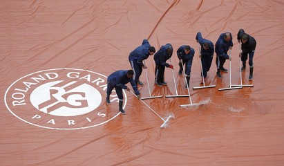 Tennis - French Open - Roland Garros - Courts crew sweep away water as rain falls at French Open