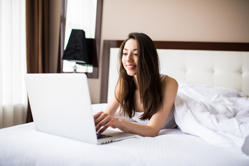 Smiling woman catching up on her social media as she relaxes in bed with a laptop computer on a lazy day