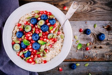 Healthy breakfast bowl oatmeal with fresh blueberries, pomegranate, mint, chia, flax and pumpkin seeds