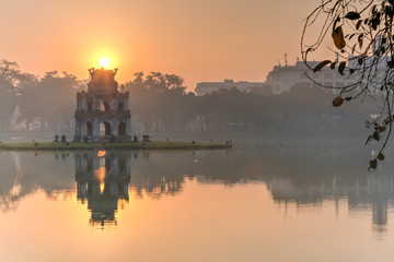 Sun rising behind the Turtle Tower in the center of Hoan Kiem Lake (Lake of the Returned Sword). The lake is one of the major scenic spots in the city and serves as a focal point for its public life.