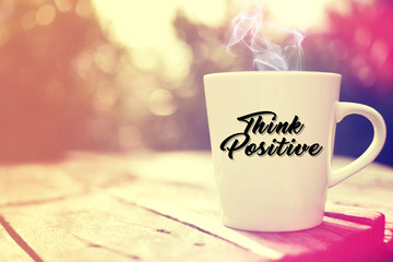 "White cup on wooden background. Written ""Think Positive""."