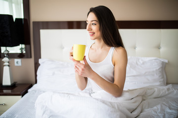 Beautiful girl at her bedroom drinking tea in the morning.