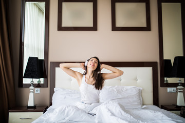 Beautiful girl in headphones is listening to music using a smartphone, looking at camera and smiling while lying on bed at home