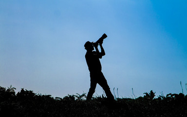Silhouette of photographer on sky background