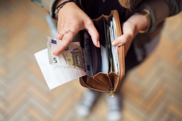 Close-up of a woman holding purse with banknotes and receipts