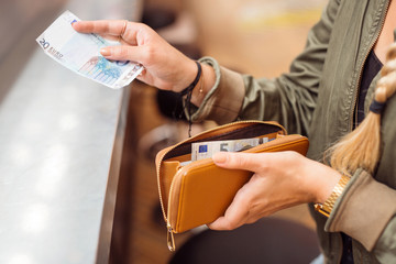 Woman paying with cash at bar
