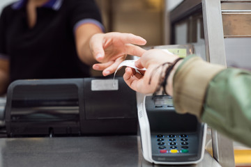 Woman taking receipt at checkout counter