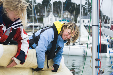 Women rolling up sail on sailboat