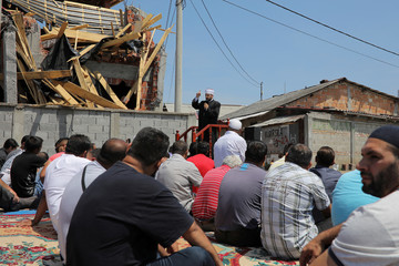 Muslims pray on a street in front of a destroyed illegally built mosque at Zemun Polje district in Belgrade