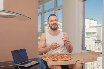 Pizza. A guy with a beard eats pizza