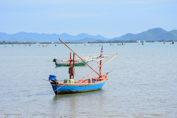 Beachfront scenery with fishing boats landing at Prachuap Khiri Khan, Thailand.