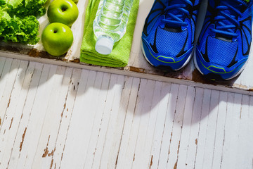 Fitness, healthy and active lifestyles Concept, dumbbells, sport shoes,  smartphone, bottle of water, apples and vegetable on wood background. copy space, top view