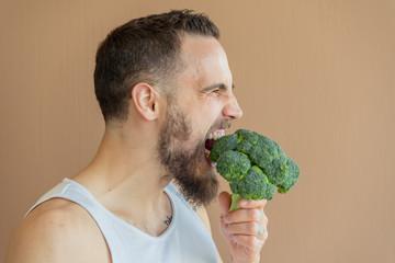 A guy with a beard sniffs broccoli