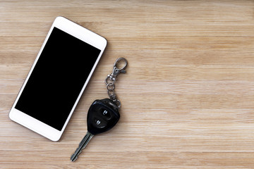 mobile phone and key on wood texture background.