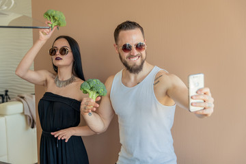 A guy and a girl with broccoli make selfies