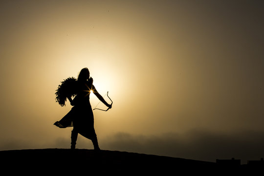 young woman with a bow and an arrow in a desert