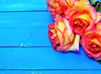 Bouquet of yellow red roses on a blue wood background