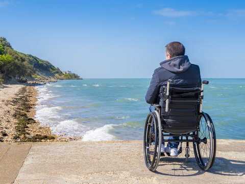 Disabled young man sitting in a wheelchair and looks at the sea.
