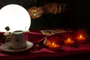 Coffee cup, candles and shiny crystal ball with tarot card in hand of fortune teller woman