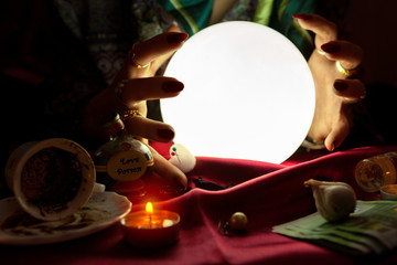 Gypsy woman put her hands around crystal ball