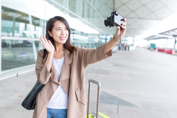 Woman taking selfie with digital camera at Hong Kong airport