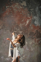 Girl dancing on a gray wall background