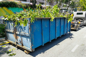 Garbage container latch with truck full of garden refuse woods