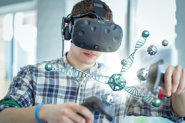 A caucasian student wearing a virtual reality headset interacts with a 3D scientific model.