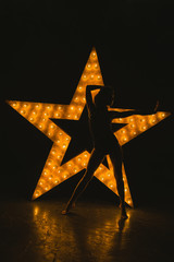 The girl is dancing against the backdrop of a glowing star