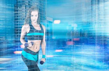 Fit girl with dumbbells in a blurred city