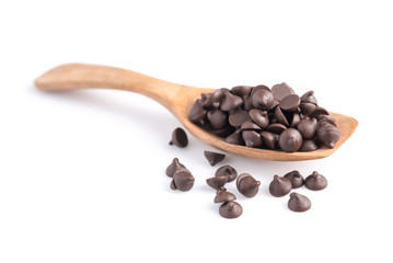 Dark chocolate chips in spoon isolated on white background.