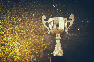 low key image of trophy over wooden table and dark background