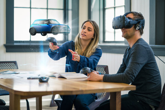 Business colleagues review automotive design concepts wearing a virtual reality headset.