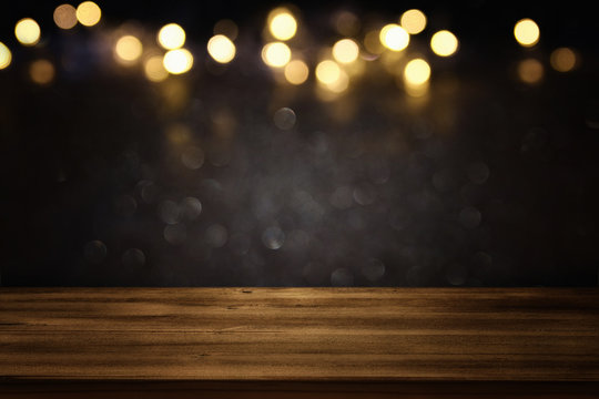 Empty table in front of black and gold glitter lights background
