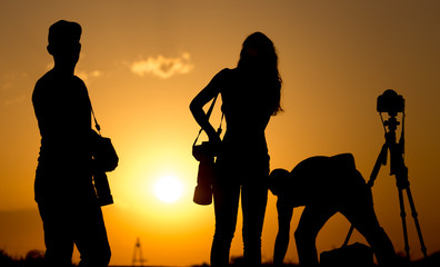 Silhouette of the girl and the man of the photographer at sunset