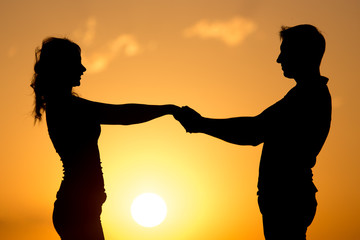 Silhouette of a guy and a girl at sunset