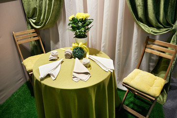 Table, chairs and bouquet of yellow flowers in vintage interior