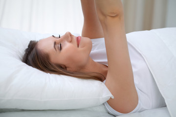 Woman stretching in bed after wake up, entering a day happy and relaxed after good night sleep. Sweet dreams, good morning, new day, weekend, holidays concept