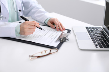 Close-up of a female doctor filling  out application form , sitting at the table in the hospital